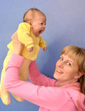 The young woman lifts on the baby's hands Stock Photos