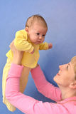 The young woman lifts on the baby's hands Royalty Free Stock Photo