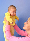 The young woman lifts on the baby's hands Royalty Free Stock Image