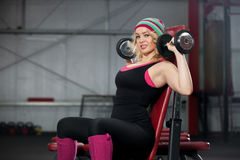 Young woman lifts dumbbells in gym Stock Photos