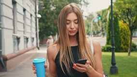 Attractive young woman with light brown hair walks down the city center, checks her smartphone and drinks coffee. Young woman with light brown hair walks down stock video footage