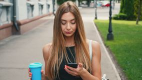 Attractive young woman with light brown hair walks down the city center, checks her smartphone and drinks coffee. Young woman with light brown hair walks down stock footage