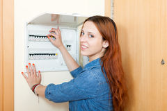 Young woman with light-switch in home Stock Image