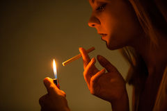 Young woman with lighter lighting up cigarette. Girl smoking. Royalty Free Stock Photo