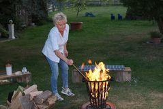 The young woman lights the campfire with a poker in her hand royalty free stock photos
