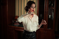 Young woman lights a cigar. Stock Photography