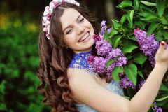 Young woman in lilac flowers Stock Images