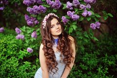 Young woman in lilac flowers Stock Photo
