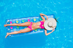 Young woman  on a lilo in the swimming pool Stock Image
