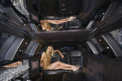 Young woman in limousine, legs crossed Stock Photos