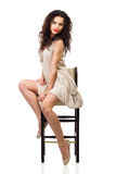 Young woman in linen dress sitting on tall chair Royalty Free Stock Photography