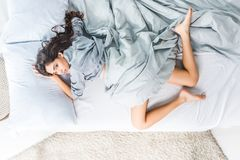 Young woman in lingerie on bed. Top view of beautiful young woman in lingerie lying on bed and looking at camera Stock Photo