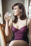 Young Woman in Lingerie Drinking Scotch Stock Photography