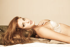 Young Woman in Lingerie Lying on Pillows Stock Image
