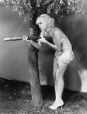 Young woman in lingerie pointing a musket at her suspect Royalty Free Stock Images
