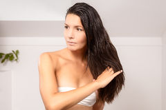 Young woman in lingerie styling her hair Royalty Free Stock Image