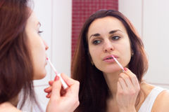 Young woman lip glossing in bathroom Stock Image