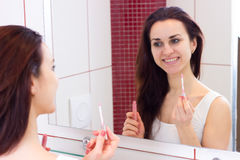 Young woman lip glossing in bathroom Royalty Free Stock Image