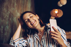 Young woman listen music with headphones and relaxing. Sitting on cafe. Domestic atmosphere. Positive emotion,closed eyes, loft interior Stock Photos