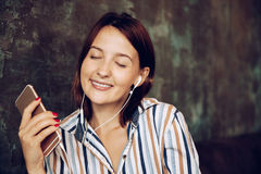 Young woman listen music with headphones and relaxing. Sitting on cafe, domestic atmosphere. Positive emotion, royalty free stock photography