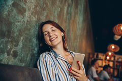 Young woman listen music with headphones and relaxing. Sitting  on cafe, domestic atmosphere. Positive emotion,closed eyes, loft i Royalty Free Stock Photos