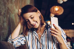 Young woman listen music with headphones and relaxing. Sitting  on cafe, domestic atmosphere. Positive emotion,closed eyes, loft i Royalty Free Stock Photo