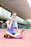 Young Woman listen to music and sitting on sport stadium Stock Images