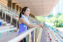 Young woman listen to music in sport arena Stock Images