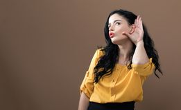 Young woman listening. On a brown background stock images