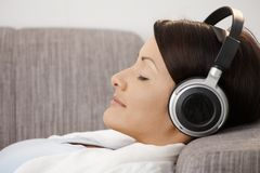 Young woman listening music. Profile portrait of young woman listening music, lying on sofa at home Stock Images
