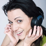 Young woman listening music. Portrait of a young woman listening music on isolated background Royalty Free Stock Photo