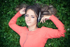 Young woman listening music. In park Stock Photo