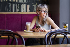 Young woman listening music in cafe Royalty Free Stock Images