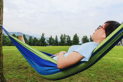 Young woman listening music on hammock  Stock Images