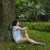 Young woman listening music. Chinese young woman listening music  with smartphone , sitting on lawn Stock Images