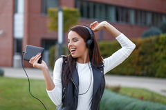 Young woman listening music and dancing outdoor. Relaxation and good mood in park Royalty Free Stock Images