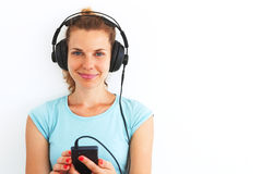 Young woman listening music with headphones. Young woman in casual dress listening music with headphones Royalty Free Stock Photography