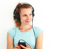 Young woman listening music with headphones. Young woman in casual dress listening music with headphones Royalty Free Stock Photo