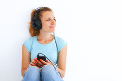 Young woman listening music with headphones. Young woman in casual dress listening music with headphones Royalty Free Stock Image