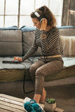 Young woman listening music in headphones in loft Royalty Free Stock Image
