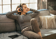 Young woman listening music in headphones in loft Royalty Free Stock Photography