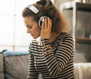 Young woman listening music in headphones in loft Stock Image