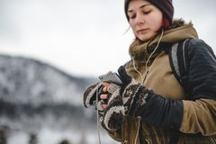 Young woman in the mountais. Mobile phone in her hands. Young woman listening the music by the headphones. Mobile phone in her hands. Winter mountains on the royalty free stock photography
