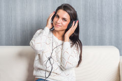 Young woman listening music with headphones in room at home on the sofa look camera stock photo