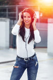 Young woman listening music by headphones. In sunset at oudorr Royalty Free Stock Photo