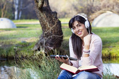 Young woman listening music with her tablet in an autumn park. Beautiful woman studying and listening music in an autumn park stock photo