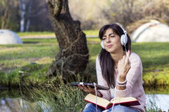 Young woman listening music with her tablet  in an autumn park Stock Photo
