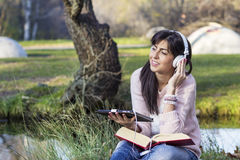 Young woman listening music with her tablet  in an autumn park Royalty Free Stock Image