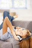 Young woman listening music laying on sofa Royalty Free Stock Photos