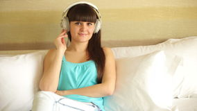 Young woman listening music and looking at window stock video footage
